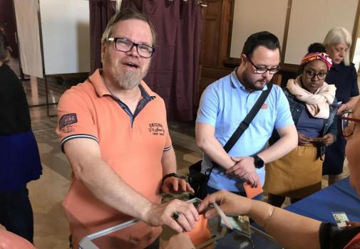 photo d'une personne en situation de handicap mettant un bulletin de vote dans l'urne
