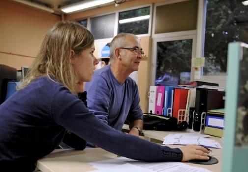 Deux personnes devant un écran d'ordinateur.