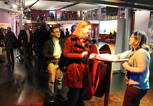 public souriant arrivant sur le lieu d'accueil d'ouverture de champ à Paris