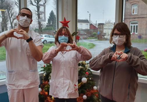 Photo du personnel soignant de LADAPT Nord faisant un coeur avec les mains devant un sapin de Noël