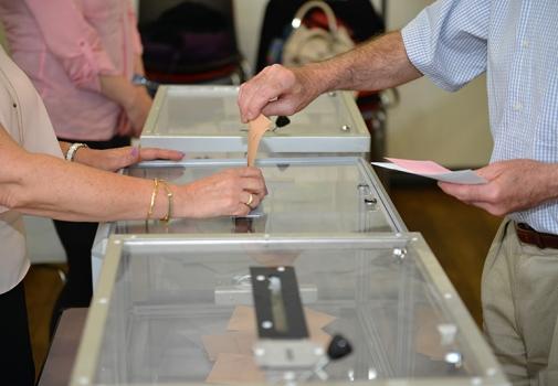 photo d'une personne mettant un bulletin de vote dans une urne