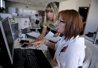 une femme aide une autre femme en situation de handicap devant son ordinateur