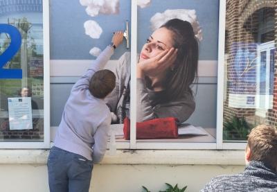 image d'une personne en train de coller une image sur une fenetre qui represente une jeune fille songeuse
