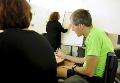 personne en fauteuil s'exprimant dans une réunion