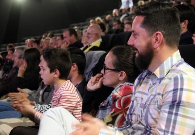 personnes riant assise dans la salle de cinéma