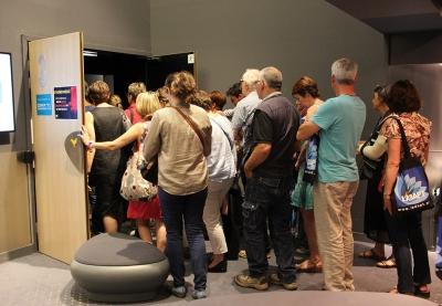 personnes entrant dans une salle de cinéma