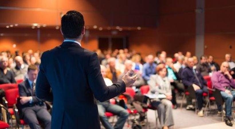 personne de dos en train de parler à une audience assise lors d'une conférence