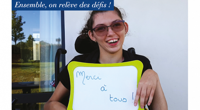 """Jeune fille en situation de handicap tient une ardoise avec une inscription """"Merci à tous"""""""