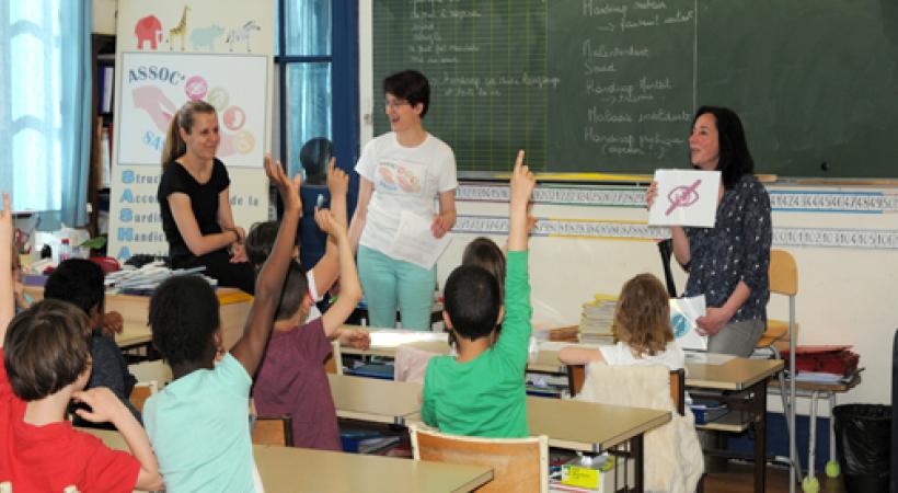 Atelier handicap dans une salle de classe avec des enfants qui lèvent la main