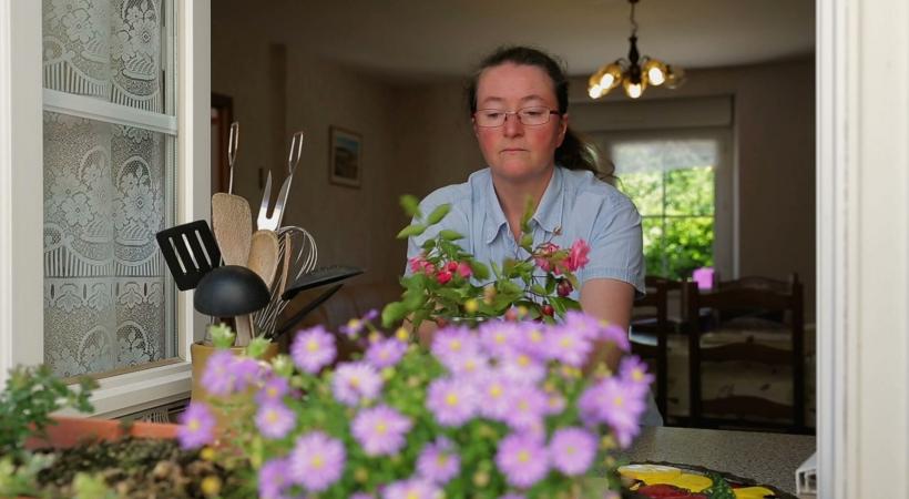 photo d'une femme en situation de handicap arrangeant ses fleurs