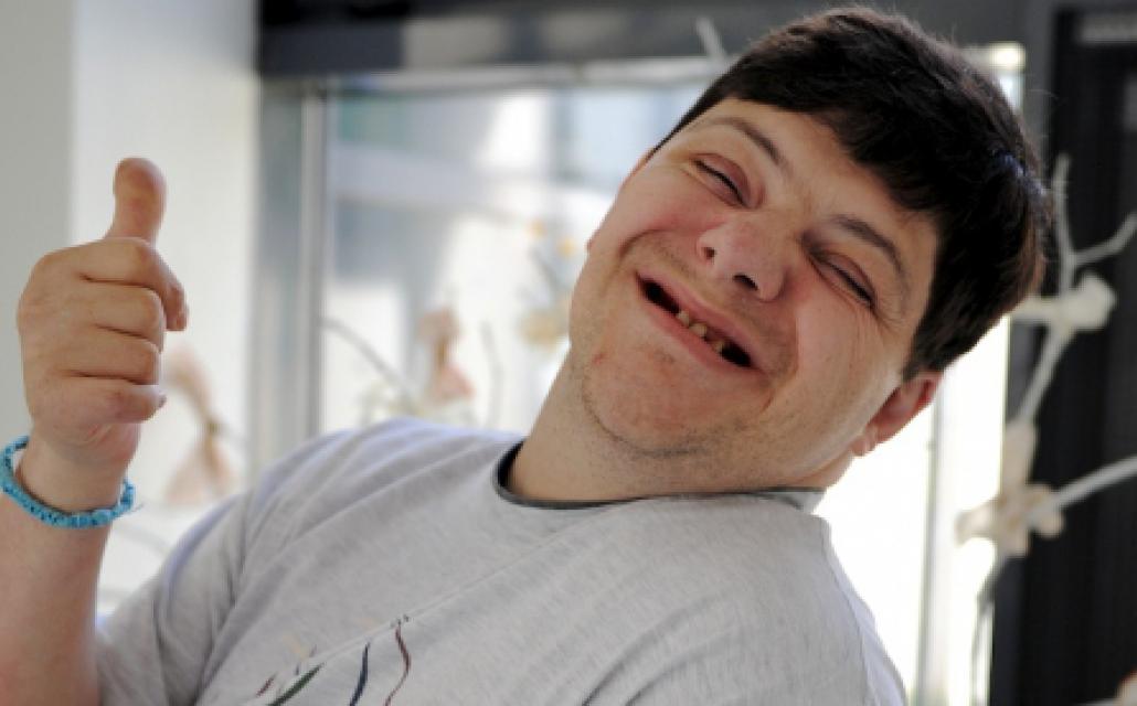 photo d'un jeune homme souriant levant le pouce en l'air