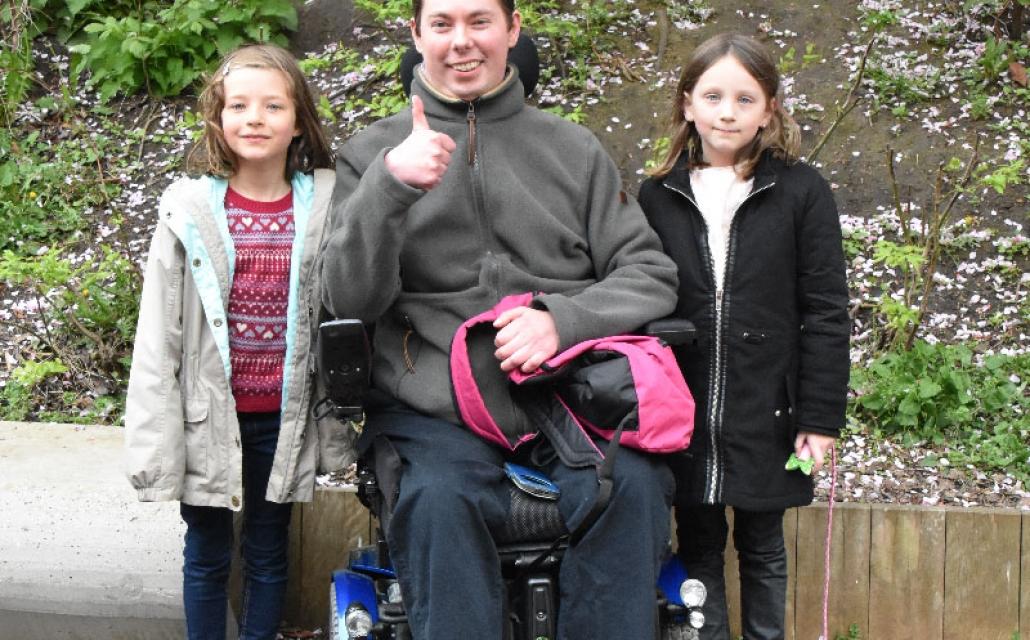un papa en situation de handicap entouré de ses deux petites filles