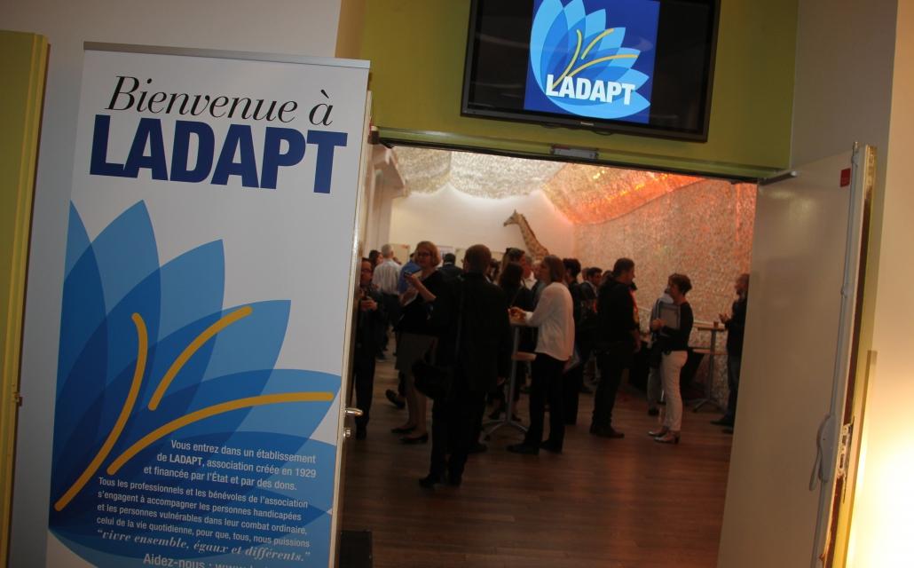 photo d'un kakemono LADAPT devant une salle dans laquelle des personnes discutent