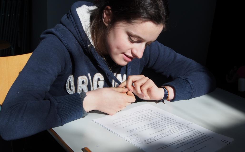 jeune fille en train d'écrire sur une feuille à un bureau