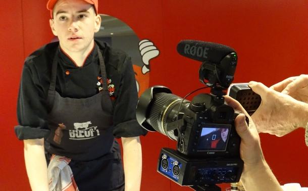 Photo d'une camera filmant un jeune homme au travail pendant le tournage d'un épisode
