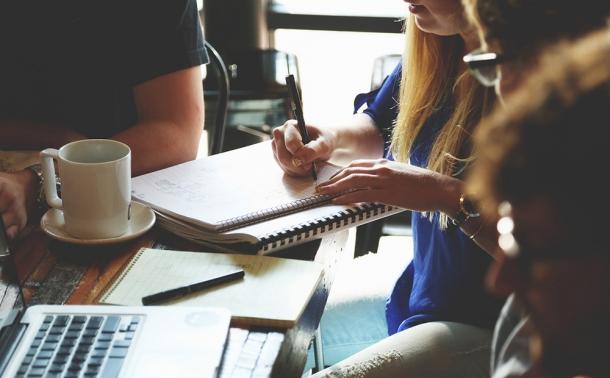 Groupe devant un café et des notes de travail discutant
