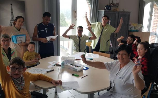 Photo de groupe : personnel de LADAPT et enfants accompagnés autour d'une table