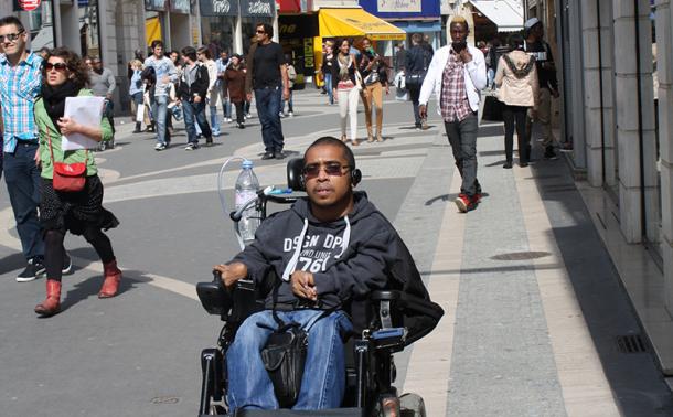 jeune homme en fauteuil dans les rues de la ville