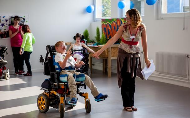 image d'un enfant en fauteuil donnant la main à une dame qui l'emmene plus loin